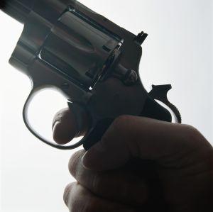 Hand holding gun, close-up