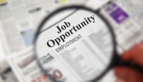"""Magnifying glass over a newspaper classified section with """"Job Opportunity"""" text"""