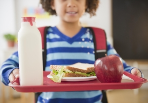African American school girl holding lunch on a tray