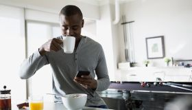 Man sipping morning coffee and texting in kitchen