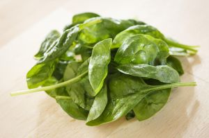Bunch of fresh spinach on a wooden table