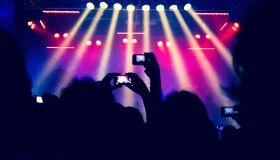Hands filming a concert