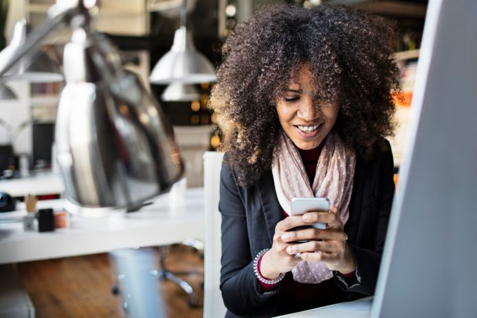 Young businesswomen texting on smartphone in the office