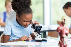 Beautiful elementary schoolgirl uses a microscope for science project