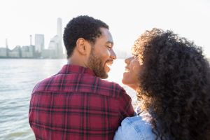Loving couple on a pier with view of city skyline