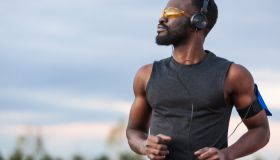 Active african american man training outdoors and listening to music