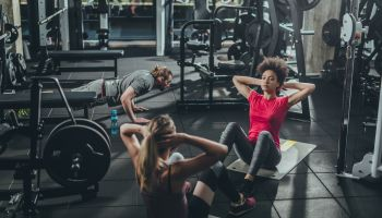 Group of athletic people having a sports training in a gym.