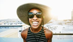 Black woman wearing sun hat and sunglasses on rooftop