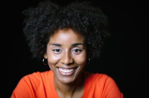Smiling Woman With Curly Hair On Black Background