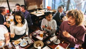 Group of mixed-raced travelers enjoying drinking alcohol in Japanese style pub