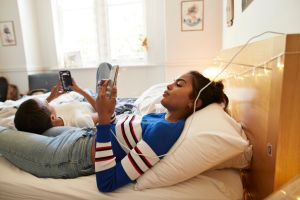 Young female friends using mobile phones in bedroom