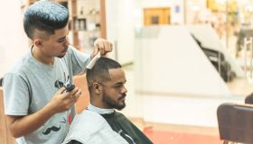 Getting haircut by barber, with electric trimmer at barbershop