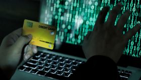 Credit Cards Theft Concept. Hacker with Credit Cards on His Laptop Using Them For Unauthorized Shopping
