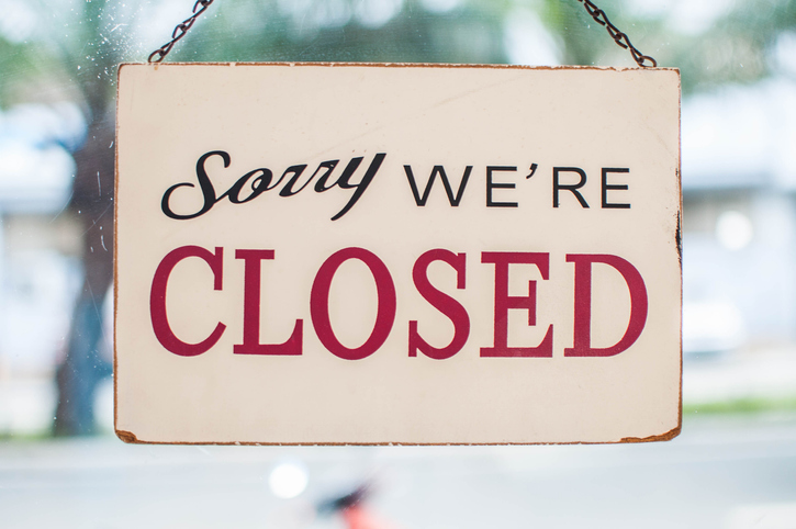 Store closed sign hanging on the window