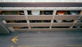 Car passing multi-story garage, overhead view (blurred motion)