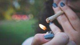 Cropped Image Of Woman Lighting Marijuana Joint