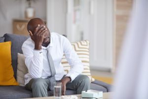 Confused young Black male patient in formalwear sitting on sofa and leaning head on hand at psychology session