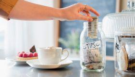 Caucasian woman putting money in tip jar