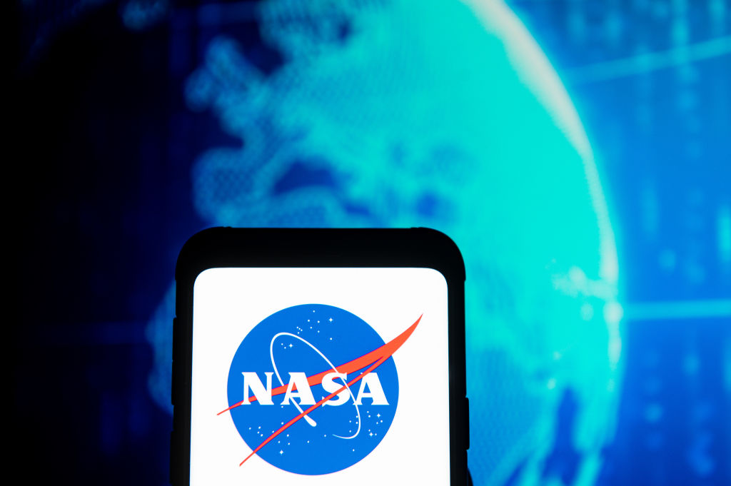 In this photo illustration a NASA logo seen displayed on a...