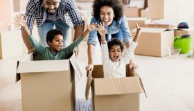Happy black parents having fun while pushing their kids in cardboard boxes at new apartment.