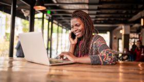 Smiling African woman using laptop.