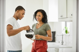 Woman looking at man pouring coffee in cup at home