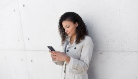 Stylish businesswoman using smart phone while standing against wall