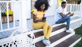 African couple sitting on stairs, having relationship problems, using smart phones
