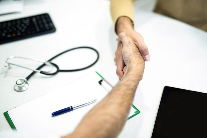 Patient and doctor shaking hands close up.