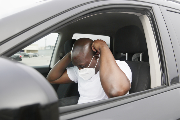 An African American millennial male put on his N95 mask in his car.