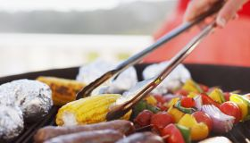 Close up of man grilling food on barbecue