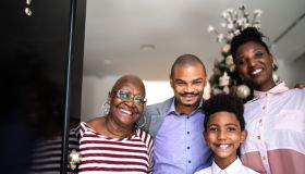 Portrait of a happy family opening the house door, christmas tree in the background
