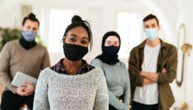 Employees posing in office with face masks