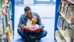Mother reading to little girl at the library