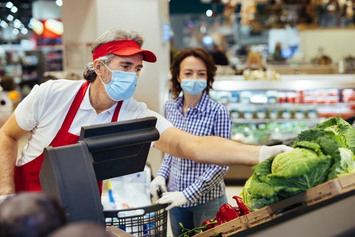 Supermarket employee helping a customer choose vegetable during coronavirus pandemic