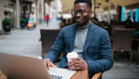 Happy young African American man working on a laptop