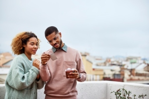 Couple Looking At Instant Print Selfie On Rooftop