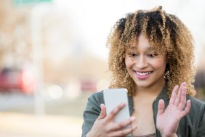 Young woman waves at friend while video chatting outdoors with smart phone