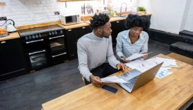 Black couple at home paying the bills online