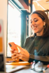 woman using mobile phone and laptop at a cafe