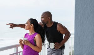 Couple on balcony with ocean view, drinking coffee