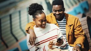 Young Afro American couple enjoying sunny day and listening to music, browsing pictures.