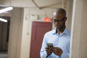 Middle-Aged bald African descent black male businessman hides to use social media