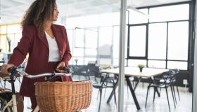 Smiling businesswoman looking away while standing with bicycle at office