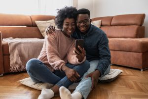 African American couple looking at smart phone at home