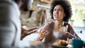 Angry African American couple arguing during breakfast at home.