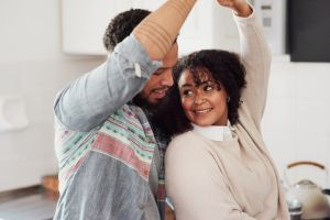 Shot of a young couple dancing in their kitchen at home