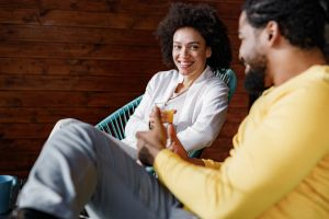 Happy black couple talking while relaxing at home.