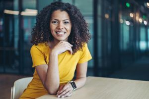 Confident young black woman sitting in the office