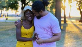Young African Couple in Love is Walking in Public Park and Feeling Happy.